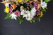 withered festive bouquet of different flowers on a dark background poster
