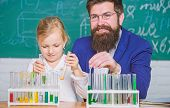 Explaining chemistry to kid. How to interest children study. Fascinating chemistry lesson. Man bearded teacher and pupil with test tubes in classroom. Private lesson. School chemistry experiment poster