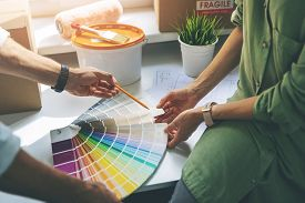 Young Couple Choosing Paint Colur From Swatch For New Home Interior