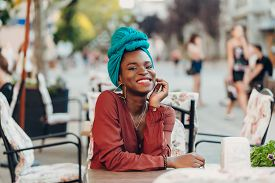 Outdoor  Portrait Of A Fashionable Muslim African Woman Wears White High-waisted Jeans, An Orange Bl