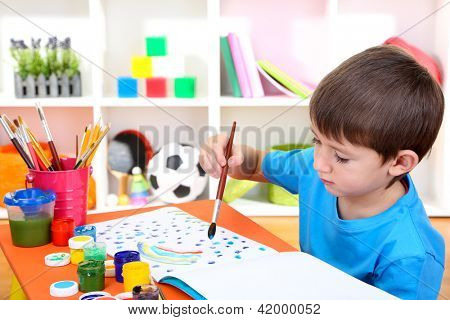 Cute little boy painting in his notebook