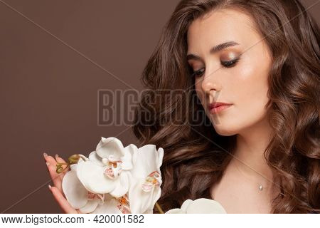 Pretty Female Model Face With Healthy Clear Skin, Brown Curly Hair And White Orchid Flowers. Facial
