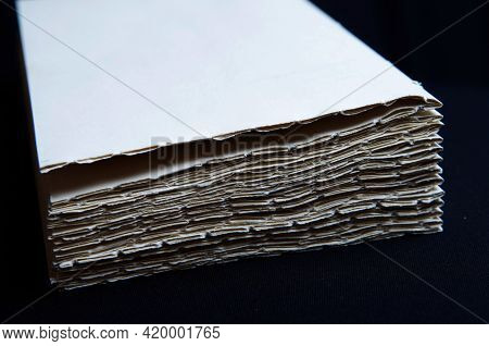 The Process Of Book Binding; Stacked Paper Folders. Black Background