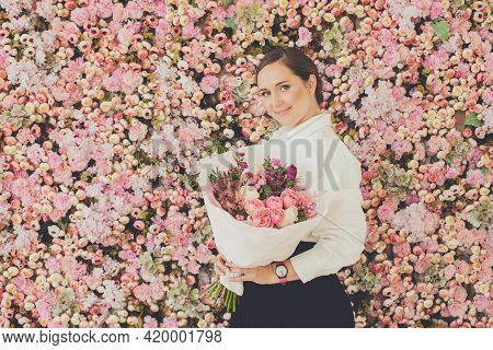 Portrait Of Beautiful Woman With Bouquet Of Flowers On Pink Roses Background