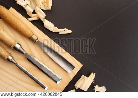 Set Of Gauges And Chisel On Wooden Plank On Black Background. Woodworking Or Carpentry Flat Lay. Top