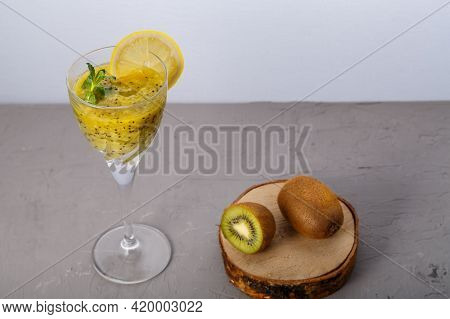 Kiwi Smoothie Garnished With Mint And Lemon In A Glass On A Gray Background Near Kiwi. Horizontal Ph