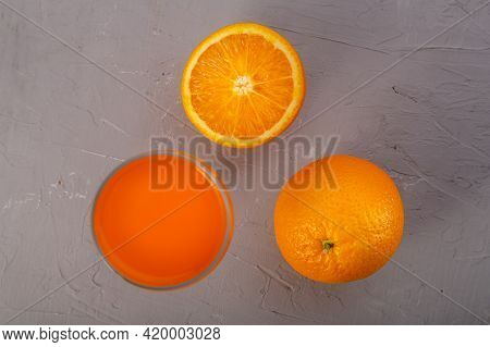 Orange Juice In A Glass Near Oranges On A Gray Background Top View. Horizontal Photo