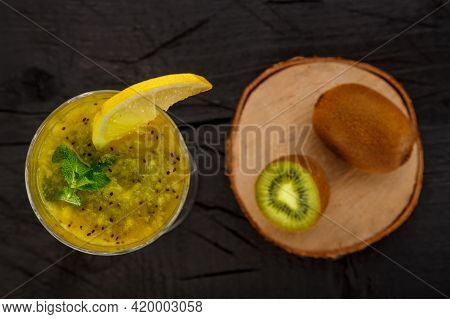 Kiwi Smoothie Garnished With Mint And Lemon In A Glass On A Black Background Near Kiwi Top View. Hor