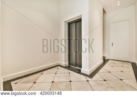 Interior Of Spacious Hallway With Metal Elevator And Tiled Floor In Contemporary Residential Buildin