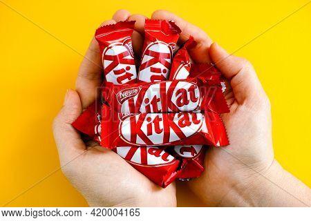 Tambov, Russian Federation - January 30, 2021 Woman Palms Full Of Kitkat Candies By Nestle. Yellow B
