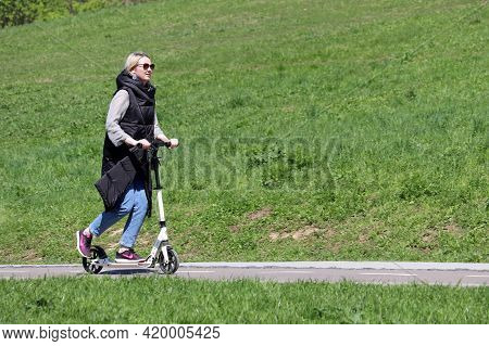 Moscow, Russia - May 2021: Young Woman In Sunglasses Rides An Electric Scooter On A Street On Lawn B