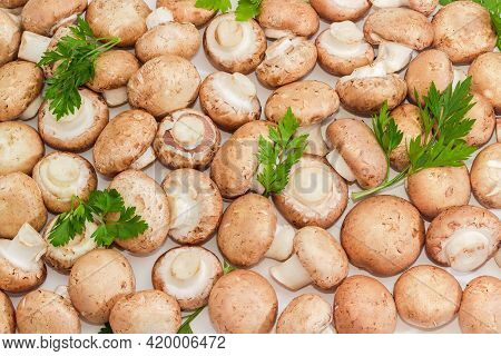 Fresh Whole Uncooked Brown Button Mushrooms With Parsley Twigs Laid Out On A Light Surface, Top View