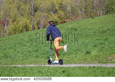 Man Rides An Electric Scooter On A Street On Green Hill Background. Riding E-scooter In Spring Or Su