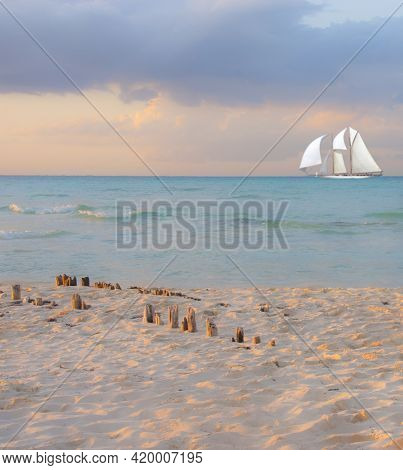 A Sunset On A Tropical Beach With A Luxury Sailing Ship On The Horizon Sailing In The Mexican Caribb