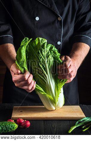 Professional Chef Or Cook Sprinkles Salt Salad Of Fresh Vegetables On Wooden Table. Preparing Health