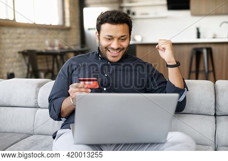 Overjoyed Indian Guy Holding Credit Card And Paying Online, Using Laptop Computer For Shopping Onlin