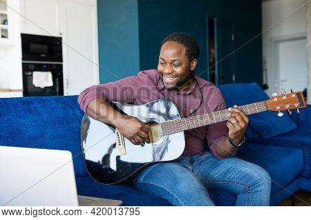 African-american Guy Playing Acoustic Guitar And Streaming And Performing Online, Sitting On The Cou