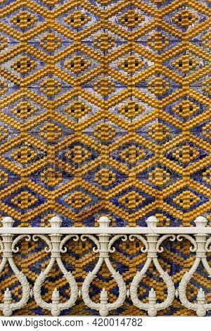 Wall Detail With Blue And Yellow Diamond Pattern And Balustrade.