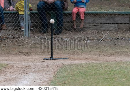 Batting Tee Set Up On Home Plate With Baseball Resting On Top For The Next Batter.