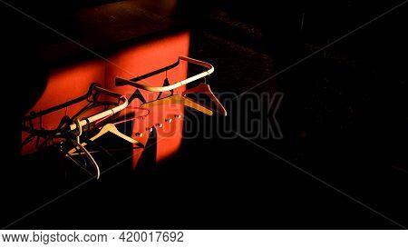 Empty Hangers In Sunlight With Red And Black Backgrounds. Abstract And Color Image.