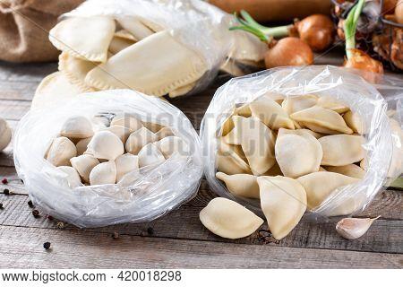 Frozen Semi-finished Products On A Wooden Table With Ingredients. Russian Dumplings. Meat Dumplings,