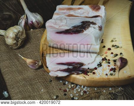 Slices Of Salted Bacon On A Dark Wooden Background. Healthy Food With Spices . Salty Fat, Lard,