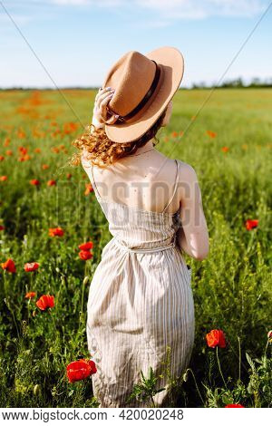Girl Posing In A Poppy Field. A Woman In A Hat With Beautiful Long Hair Stands In The Middle Of A Be