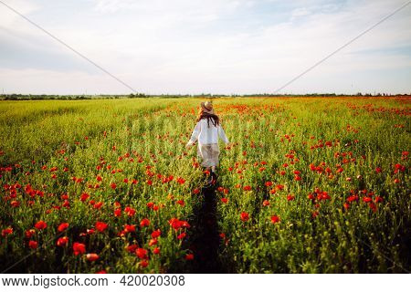 A Young Woman Stands In A Beautiful Blooming Garden With Red Flowers. A Girl In A Hat Walks Through