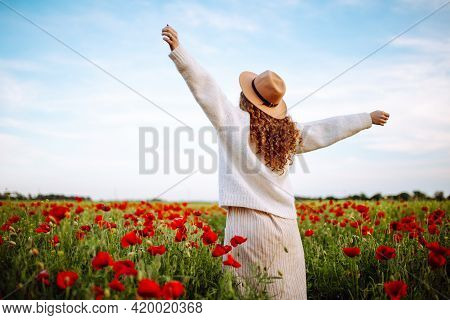 Woman Posing In A Poppy Field. A Girl With Curls In A Hat Stands In The Middle Of A Blooming Field W