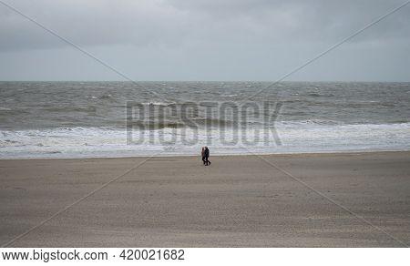 Panorama View Of Elderly Couple Walking Along Sand Beach Near Westkapelle Domburg Veere Zeeland Neth
