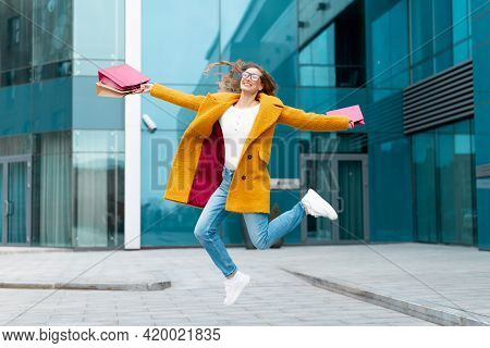 Business Woman With Shopping Bags Dressed Yellow Coat Jumping With Happiness Outdoors Corporative Bu