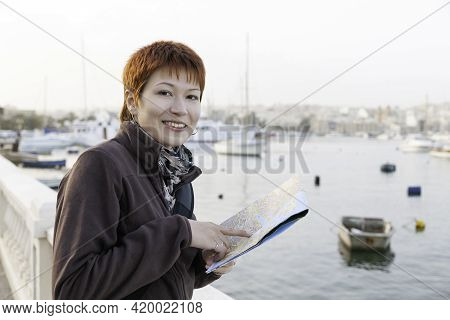 Woman With Short Red Haircut Reads Malta Map. Curious Woman Stands Near Msida Yacht Marina. Europe T