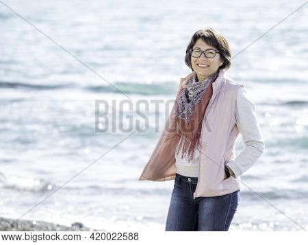 Smiling Woman Walking On Seaside. Vacation On Ocean Coast. Turquoise Water Behind Woman With Happy S