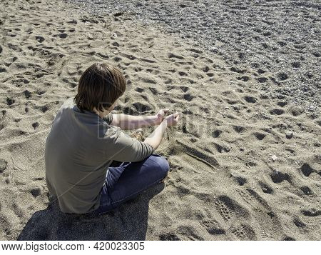Man Relaxes On Sandy Beach And Pours Sand From Hand To Hand. Peaceful Leisure Activity At Warm Seaso