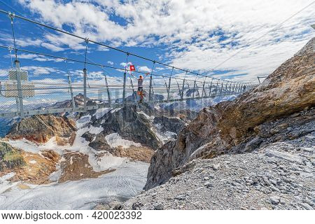 Woman On Suspension Bridge Waving A Swiss Flag. Titlis Cliff Walk With Glacier In The Uri Alps. View