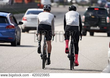 Two Cyclists Ride On A Highway Loaded With Cars. Selective Focus.