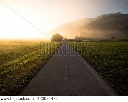 Early Morning Sunrise Panorama Of Asphalt Concrete Biking Path Road In Green Nature Landscape Near I