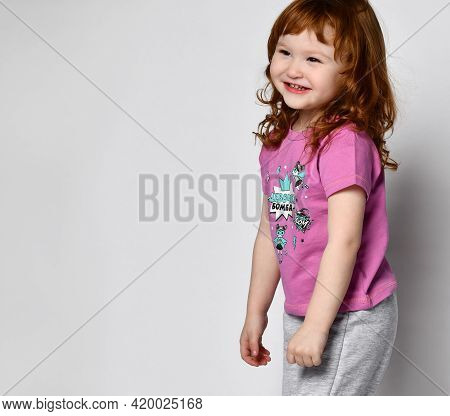 Shy Smiling Little Girl Smiling Cutie Baby In Sportswear Studio. Little Adorable Girl Laughs Out Lou