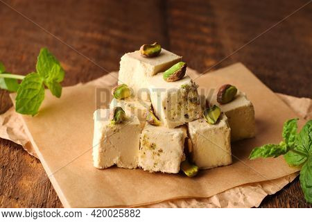 Halva With Pistachios On Parchment Paper On A Wooden Background. Natural Vegan Product. Turkish, Ara