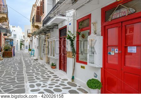 Paros, Greece - September 28, 2020: Greek Street With Red Doors And Whitewashed Pavement In Old Town