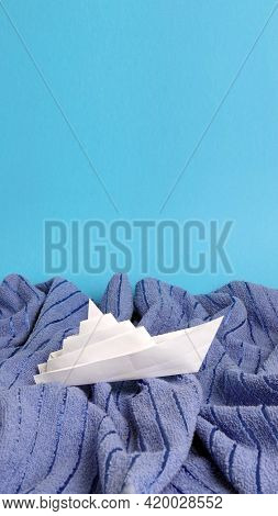 White paper ship toy on blue towel waves abstract concept photo of turbulent sea or ocean on blue copy space background