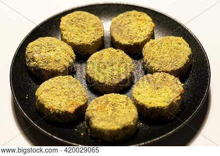 Frozen Veggie Nuggets With Lentils And Greens On A Black Plate