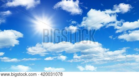 Sunny day background, blue sky with white cumulus clouds, natural summer or spring background with perfect hot day weather.