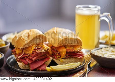 Delicious pastrami meat sandwiches served with glass of beer, pickles, potato chips and sides.