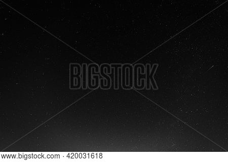 A Starry Sky With Many Stars And A Flying Meteor