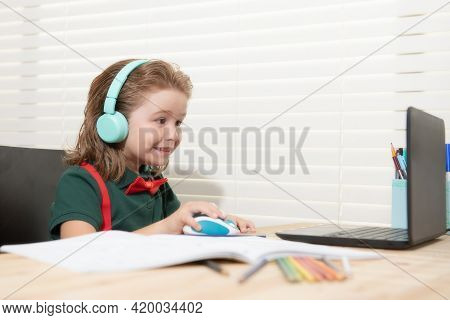 Child Boy In Headphones Using A Laptop At Home. Homeschooling, Distant Learning, Online Elearning.