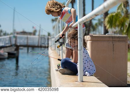 Couple Of Children Fishing. Kids On Pier. Child At Jetty With Rod. Boy And Girl With Fish-rod.