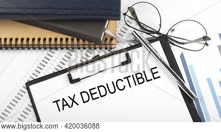 Text Tax Deduction On Office Desk Table With Notebooks, Supplies,analysis Chart, On The White Backgr