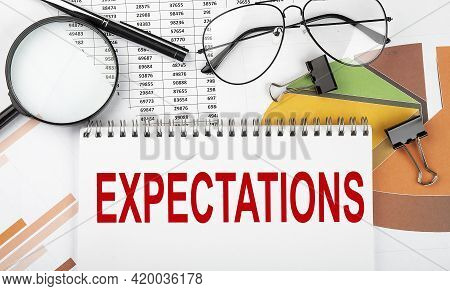 Text Expectations On White Paper Notebook On The Diagram. Business