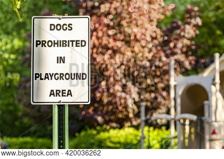 Dogs Prohibited In Playground Area Sign In Front Of The Fences At A Fenced Playground Of A Residenti